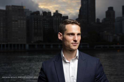 Model Andy Mizerek with background of New York skyline at dusk.